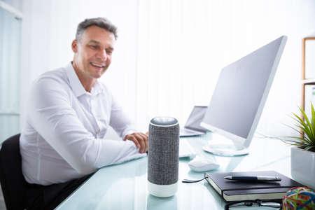 Foto de Smiling Mature Man Listening To Music On Wireless Speaker - Imagen libre de derechos