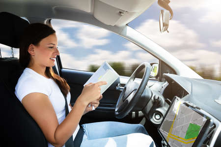 Young Woman Looking At Diary While Sitting In Self Driving Modern Car