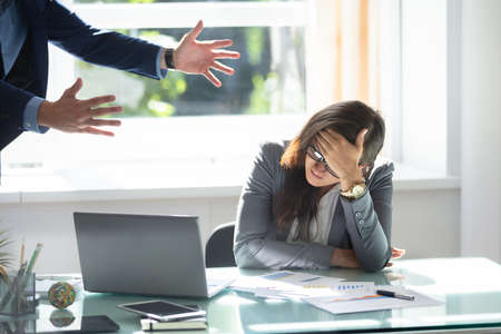 Photo pour Businessman Scolding Stressed Female Employee Sitting In Office - image libre de droit