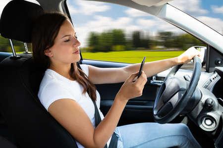 Photo pour Close-up Of A Woman's Hand Typing Text Message On Cellphone While Driving Car - image libre de droit