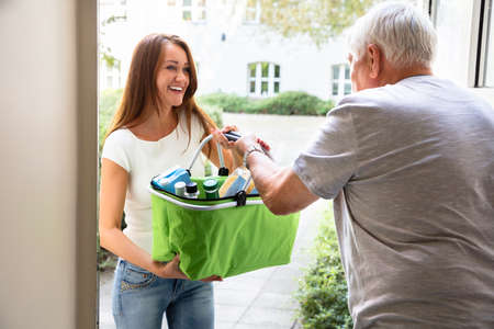 Photo for Senior Man With Walking Stick Offering Help To His Young Daughter Carrying Groceries - Royalty Free Image