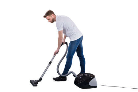 Foto de Man Using Vacuum Cleaner On White Background - Imagen libre de derechos