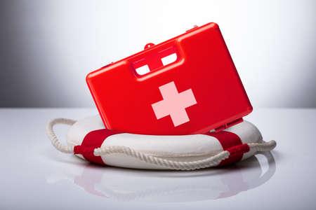 Photo pour Close-up Of First Aid Kit And Lifebuoy On Reflective Desk - image libre de droit