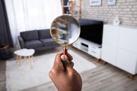 Photo pour Man Searching In The House With Magnifying Glass - image libre de droit