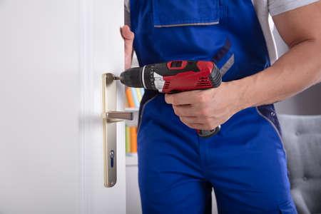 Foto de Midsection View Of A Man's Hand Installing Door Knob With Wireless Screwdriver - Imagen libre de derechos