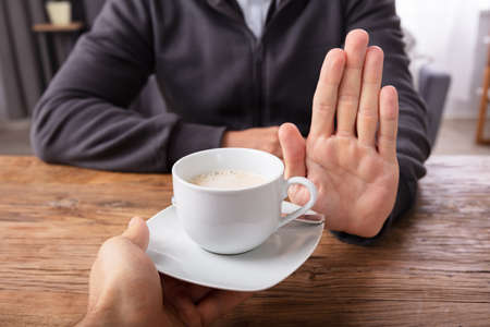 Foto de Close-up Of A Man's Hand Refusing Cup Of Coffee Offered By Person Over Wooden Desk - Imagen libre de derechos