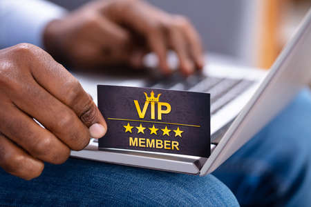 Close-up Of A Man's Hand Holding VIP Member Card While Using Laptop
