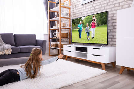 Photo pour Girl Lying On Carpet Watching Television At Home - image libre de droit