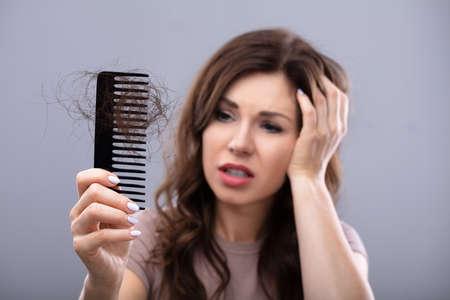 Foto de Close-up Of A Worried Woman Holding Comb Suffering From Hairloss - Imagen libre de derechos