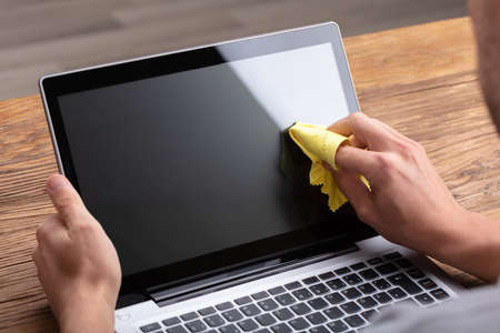 Photo pour Man Cleaning Laptop Screen With Soft Yellow Cloth - image libre de droit