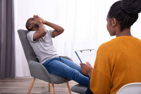 Photo pour Female Psychologist With Clipboard Sitting Near Young Man Suffering From Depression - image libre de droit
