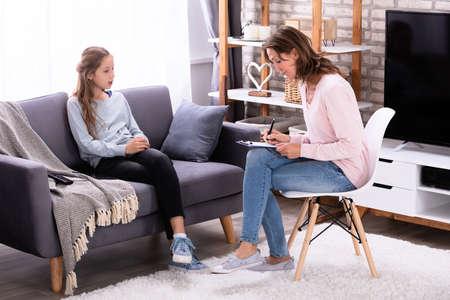 Photo pour Girl Sitting On Sofa Explaining Her Problems To Female Psychiatrist At Home - image libre de droit