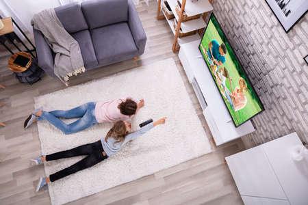 Foto de Mother And Daughter Lying On Carpet Watching Television At Home - Imagen libre de derechos