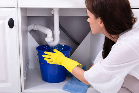 Photo for Close-up Of A Young Woman Placing Blue Bucket Under Water Leaking From Sink Pipe - Royalty Free Image