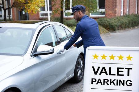 Photo pour Happy Male Valet Opening Car Door Near Valet Parking Sign - image libre de droit