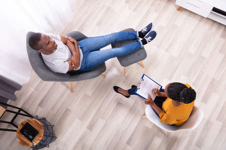 Photo pour Young African Man Sitting On Chair Near Female Psychologist With Clipboard - image libre de droit