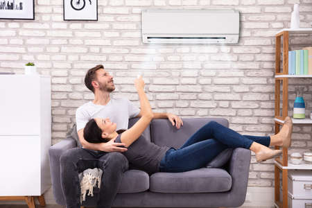 Photo pour Happy Young Couple Sitting On Sofa Operating Air Conditioner At Home - image libre de droit