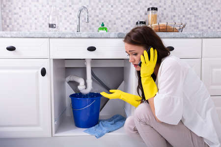Photo for Sad Young Woman Calling Plumber In Front Of Water Leaking From Sink Pipe - Royalty Free Image