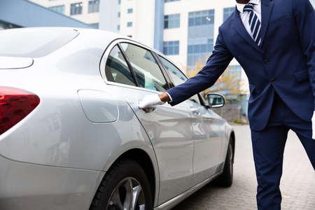 Photo pour Valet's Hand Opening Grey Car Door On Street - image libre de droit