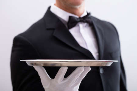 Photo pour Close-up Of Waiter's Hand Holding Empty Silver Tray Against White Background - image libre de droit
