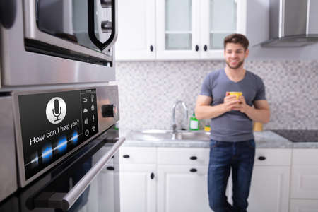 Foto de Happy Young Man Looking At Oven With Voice Recognition Function In Kitchen - Imagen libre de derechos