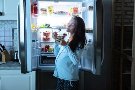 Foto de Pregnant Woman Eating Pickle From Jar In Front Of An Open Refrigerator - Imagen libre de derechos