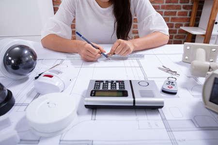 Foto de Close-up Of A Female Architect Drawing Blueprint With Pencil On Desk In The Office - Imagen libre de derechos