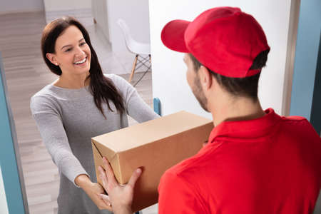 Photo pour Happy Young Woman Accepting Cardboard Box From Delivery Man - image libre de droit