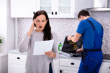 Photo for Young Housewife Shocked After Reading Repair Cost Estimate Of Domestic Appliance - Royalty Free Image