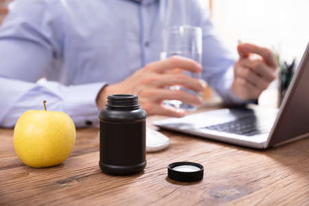 Photo pour Apple And Pills Bottle In Front Of Businessman Taking Medicines In Office - image libre de droit