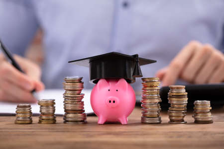 Photo pour Stacked Coins And Piggy Bank With Graduation Cap In Front Of Businessman - image libre de droit
