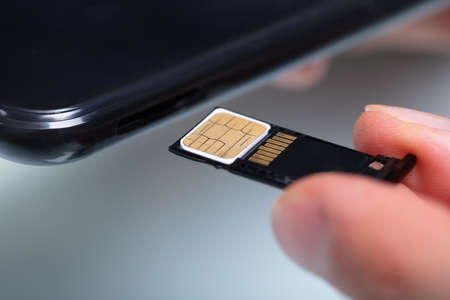Photo pour Close-up Of A Person's Hand Inserting Sim Card In Cellphone - image libre de droit
