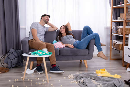 Photo pour Smiling Couple Relaxing On Sofa In Messy Living Room At Home - image libre de droit