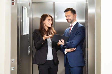 Photo pour Smiling Young Businesswoman And Businessman Discussing While Using Digital Tablet Standing Near Elevator - image libre de droit