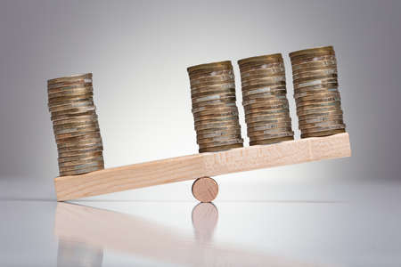 Foto de Stack Of Coins On Wooden Seesaw Over Gray Background - Imagen libre de derechos
