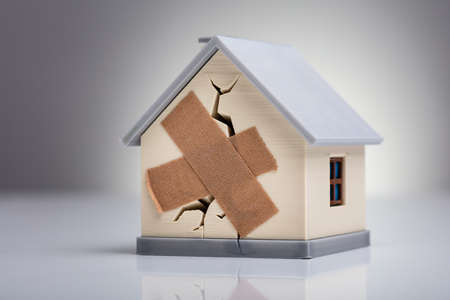 Foto de Broken House Model With Crossed Band Aid On Desk - Imagen libre de derechos