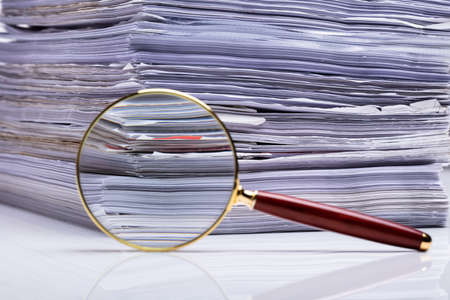 Photo pour Close-up Of Magnifying Glass On Background Of The Stacked Paper Files - image libre de droit