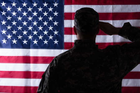 Foto per Rear View Of Military Man Saluting Us Flag - Immagine Royalty Free