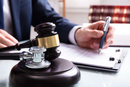 Photo pour Judge Writing On Legal Documents With Mallet And Stethoscope Over Sound Block In Court - image libre de droit