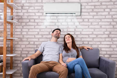 Photo for Happy Young Couple Sitting Under Air Conditioner On Couch At Home - Royalty Free Image