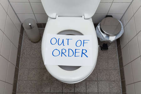 Photo pour Written Text Out Of Order Message On Paper Over Toilet Bowl In Bathroom - image libre de droit