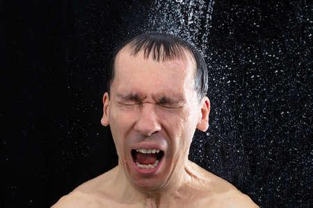 Photo pour Portrait Of Young Man Taking Cold Shower In Bathroom - image libre de droit