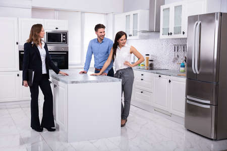 Photo pour Professional Real Estate Agent Showing Refrigerator In House To A Young Couple - image libre de droit