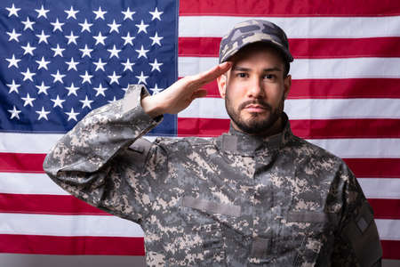 Foto per Portrait Of A Male Solider Saluting Against The American Flag - Immagine Royalty Free