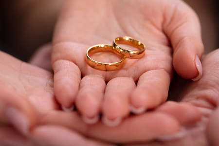 Photo pour Man And Woman's Hand With Pair Of Golden Engagement Rings - image libre de droit