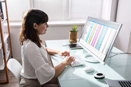 Photo pour Side View Of Businesswoman's Hand Analyzing Data On Computer Over Desk - image libre de droit