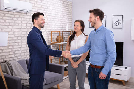 Photo pour Smiling Male Real Estate Agent Shaking Hands With His Clients In New Home - image libre de droit