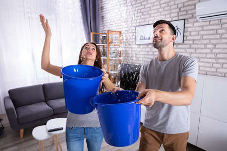 Photo pour Young Husband And Wife With Blue Bucket Collecting Water From Damaged Ceiling In Living Room - image libre de droit