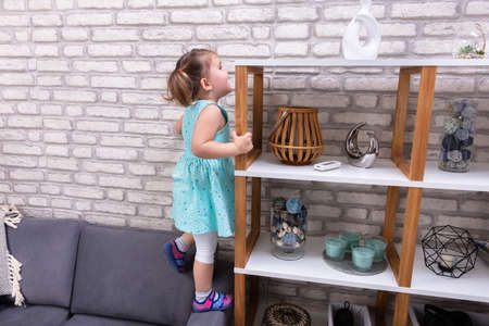 Photo pour Cute Toddler Girl Standing On Sofa And Reaching For Toys On Shelf - image libre de droit