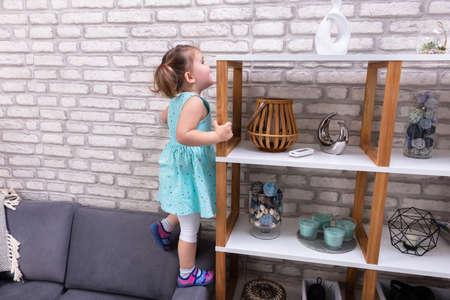 Foto de Cute Toddler Girl Standing On Sofa And Reaching For Toys On Shelf - Imagen libre de derechos